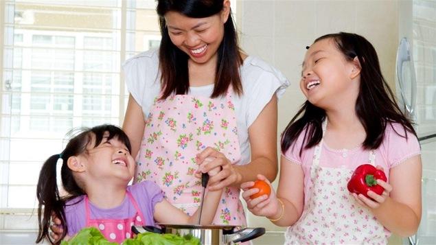 Une mère cuisine avec ses deux filles