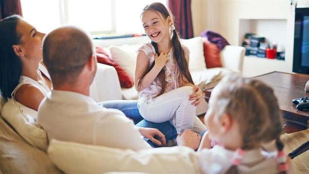 Un couple et deux petites filles qui sourient dans un salon