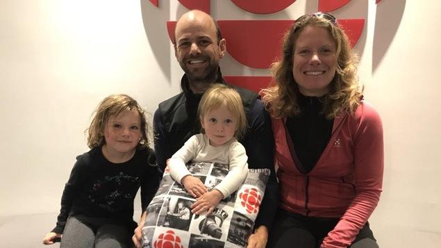 Un couple et leurs deux filles de 6 et 2 ans, assis devant un logo de Radio-Canada