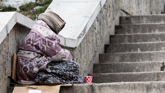 Profil d'une femme emmitouflée dans ses vêtements et assise dans un escalier.