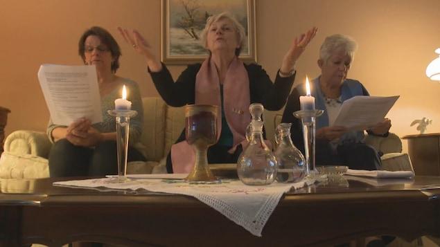Tois femmes avec Marie Bouclin au centre célèbrent l'eucharistie
