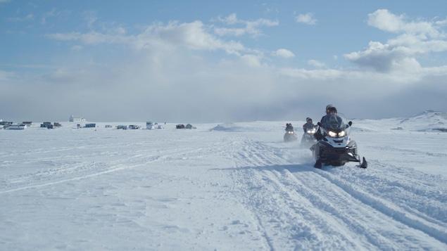 Des motoneigistes circulent sur la Route blanche près d'un village de la Basse-Côte-Nord.
