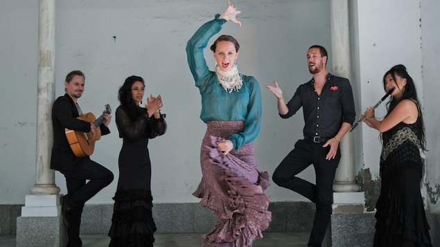 Une femme danse le flamenco pendant que quatre musiciens jouent derrière elle.