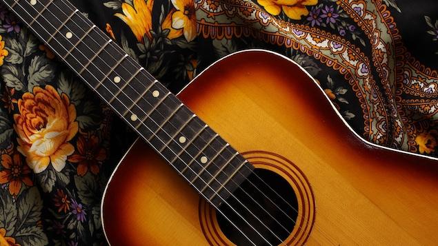 Une guitare acoustique en bois déposée sur un foulard fleuri rappelant le flamenco.