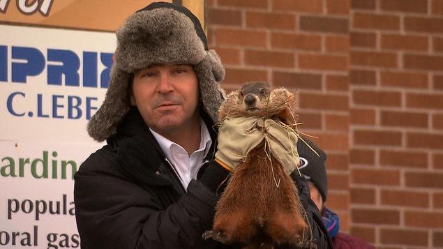 Un homme tient une marmotte dans ses mains