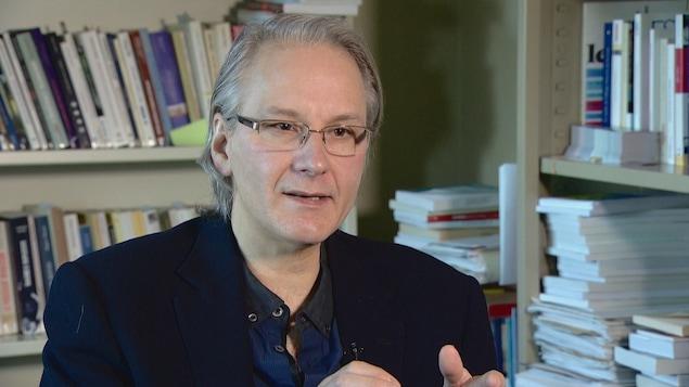 Le politologue Frédéric Boily dans son bureau, avec des bibliothèques remplies de livres derrière lui.