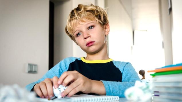 Un jeune homme triste devant ses livres d'école.