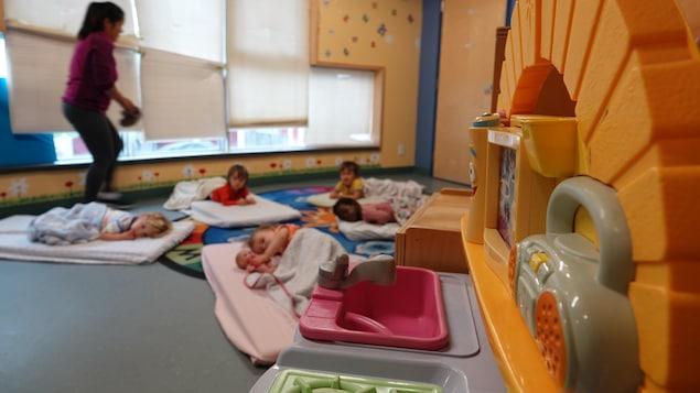 Des enfants couchés sur des matelas disposés à terre et l'éducatrice qui passe à travers la salle.