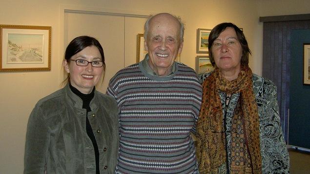 Trois personnes prennent la pose dans une galerie d'art. Il y a des tableaux accrochés sur le mur derrière eux.