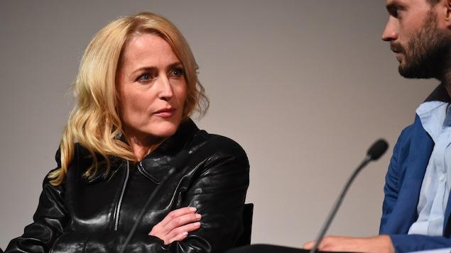 Gillian Anderson, assise les bras croisés, regarde son collègue, Jamie Dornan, qui est tournée vers elle.