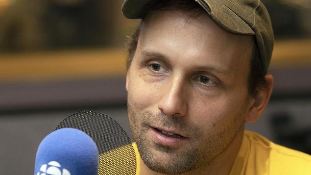 Un homme portant une casquette parle devant un micro.