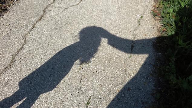 Un adulte touche la tête d'une fillette.