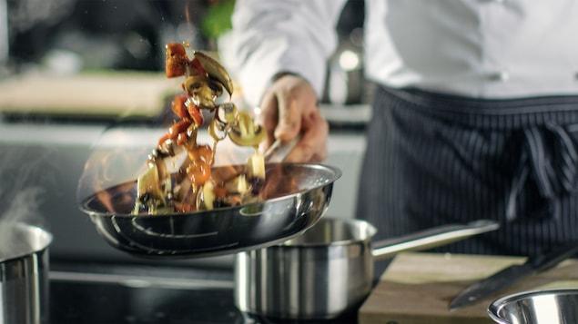 Un cuisinier à l'oeuvre dans la cuisine d'un restaurant.