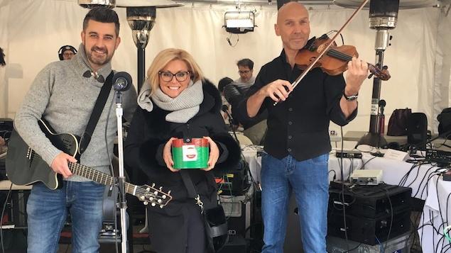 Un homme avec un guitare, une femme tenant une petite boîte et un homme tenant un violon.