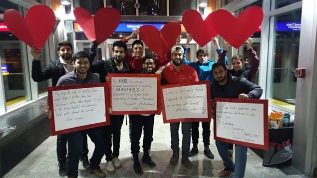Des jeunes tiennent des messages et de coeurs rouges dans une station de train léger