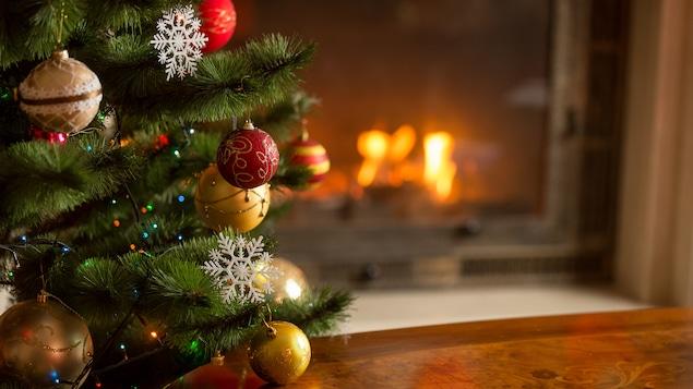 Un sapin de Noël décoré de boules et de guirlandes lumineuses devant un feu de cheminée