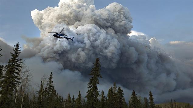 Un hélicoptère survole un feu de forêt.