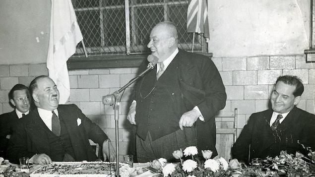 Le maire Camillien Houde, debout au centre, fait rire ses convives, dont le conseiller municipal Max Seigler.