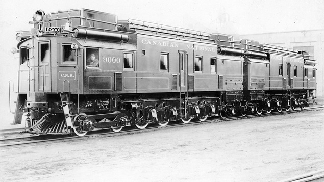 Photo en noir et blanc d'une locomotive de train du Canadian National avec un homme dans la cabine avant.