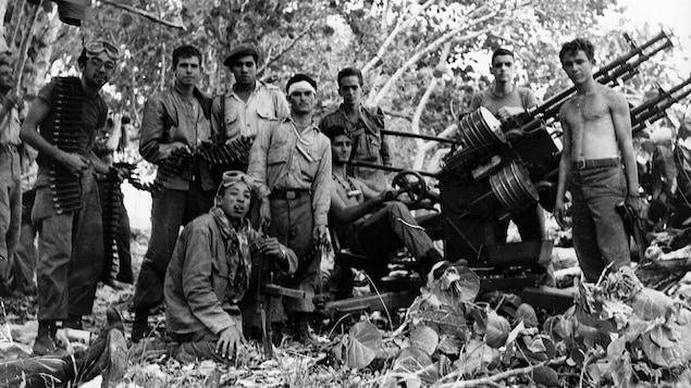 Une douzaine d'hommes posent en pleine forêt devant de l'artillerie.
