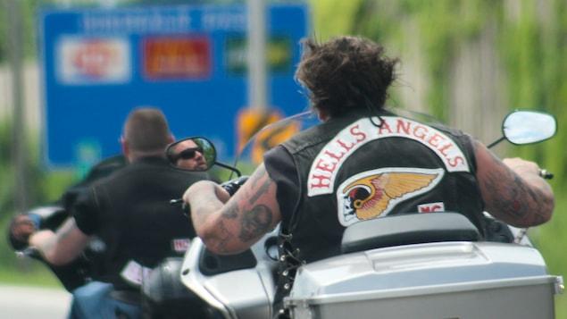 Deux motards des Hells Angels circulent sur une autoroute.