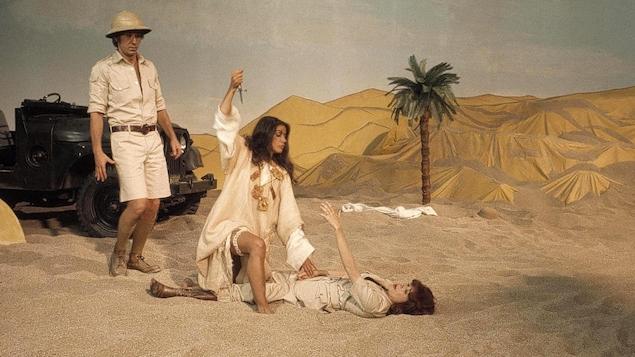 Dans un désert recréée en studio, une femme avec un genou au sol s'apprête à poignarder une autre femme couchée, tandis qu'un homme regarde la scène derrière elles.