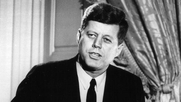 Photo en noir et blanc d'un homme qui parle devant une tribune et des micros.