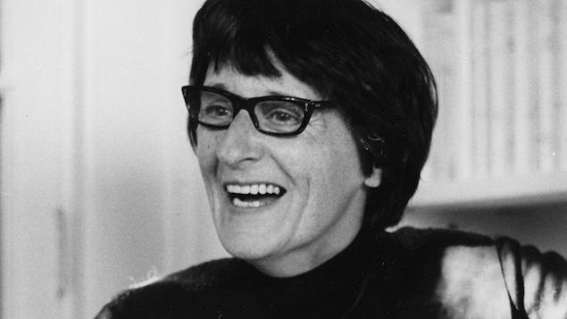 Françoise Loranger regarde à droite en souriant.