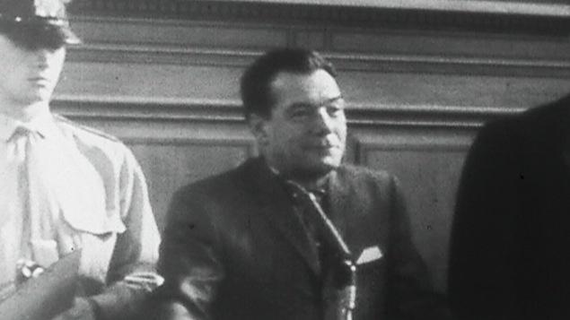 En 1965, Lucien Rivard est entouré de policier lors de sa comparution.