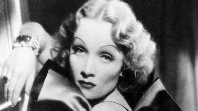 Photo en noir et blanc d'une femmes des années 1930 qui regarde la caméra.