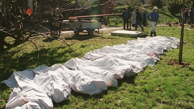 Photo prise à l'extérieur sur laquelle on voit plusieurs corps au sol recouverts de draps blancs.