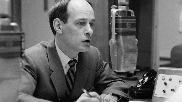 Dans un studio de radio, l'animateur René Lévesque, une cigarette à la main, derrière un micro suspendu.