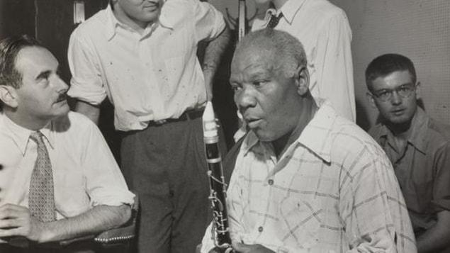 Un homme assis tient un saxophone dans ses mains. Quatre hommes, dont deux debouts, l'entourent.