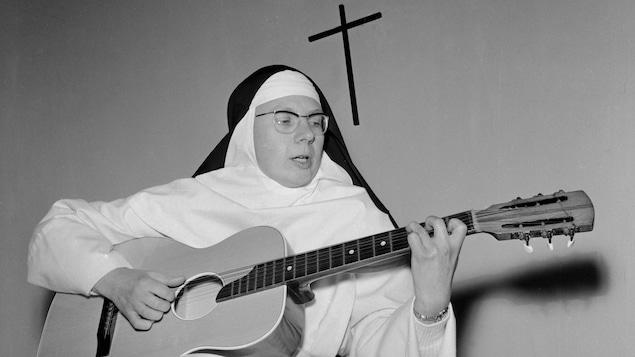 Soeur Sourire chante avec sa guitare dans un couvent, en Belgique. Un crucifix est accroché au mur derrière elle.