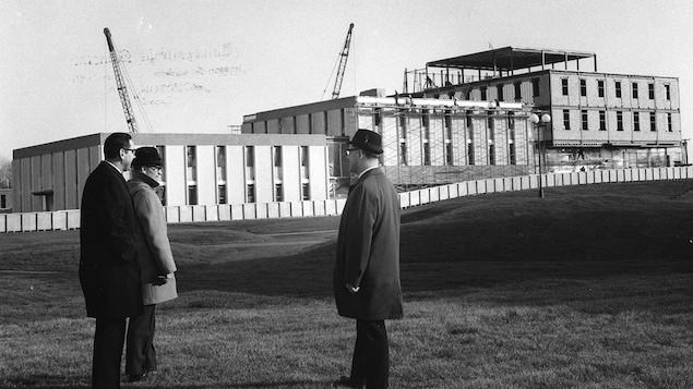 Trois hommes regardent l'Université de Moncton en construction.