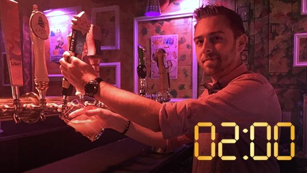 Un homme derrière un comptoir dans une boîte de nuit sert une bière pression.