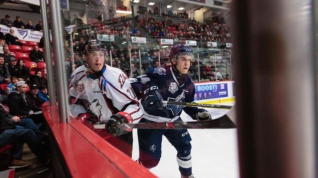 Deux joueurs de hockey le long de la baie vitrée lors d'un match.