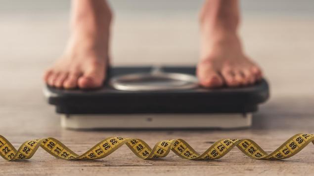 Une photo montrant les pieds d'une personne sur une balance. En avant-plan, un ruban à mesurer est visible.