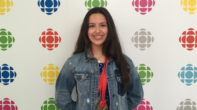 A girl in front of a Radio-Canada poster.