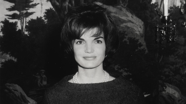 Jacqueline Bouvier Kennedy en 1961, souriant à la caméra (photo en noir et blanc)