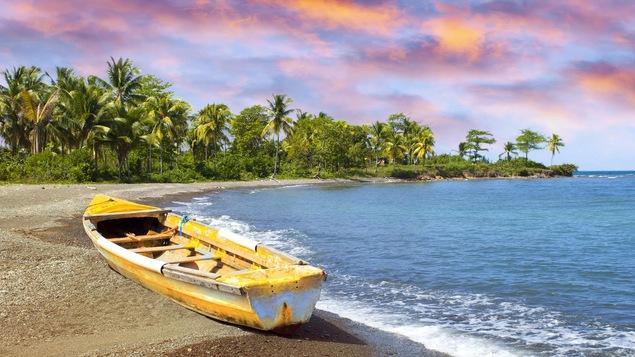 Une bateau de pêcheur traditionnel sur une plage au moment d'un couché de soleil.