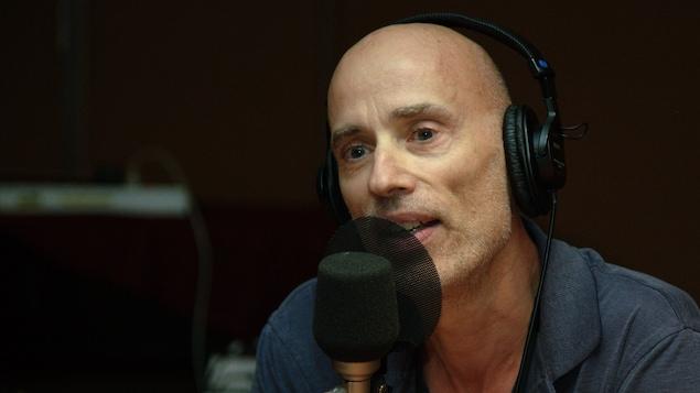 James Hyndman parle derrière un micro, des écouteurs sur la tête.