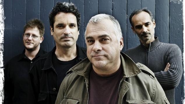 Pochette d'album du groupe Auguste, on y voit les 4 membres du groupe debout devant un mur.