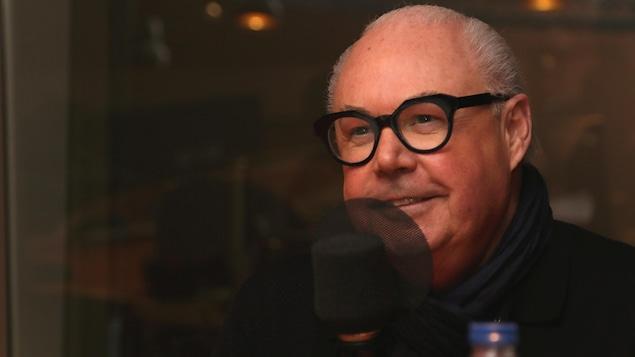 Jean-Claude Poitras souriant dans un studio de radio.