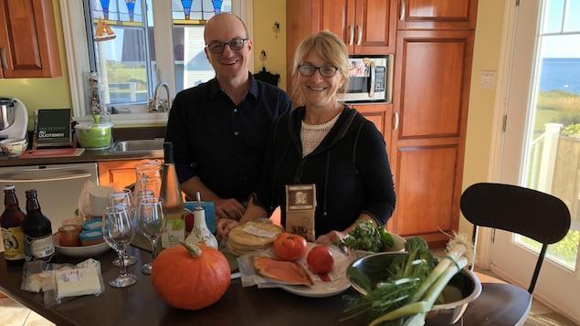 Jean-Marie Perreault et Chantal Bourdages posent dans leur cuisine entourés d'aliments gaspésiens
