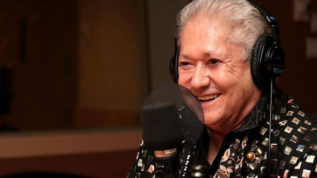 Jean-Paul Daoust souriant dans un studio de radio.