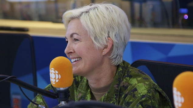 Une femme aux cheveux courts blonds et blancs sourie devant un micro orange dans un studio de radio.