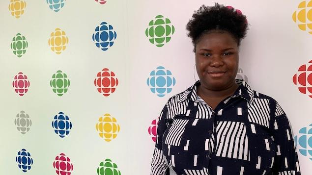 Une jeune fille devant un mur de logos de Radio-Canada.