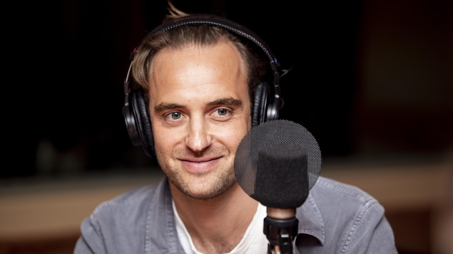 Il sourit au micro.