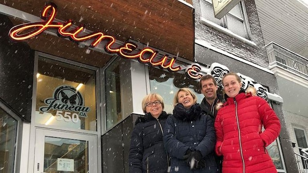 En hiver, trois femmes et un homme  devant le commerce Juneau et Frères